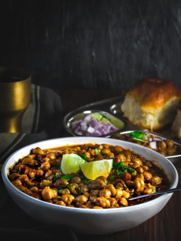 Chana masala served in a white bowl with side of lemon. On the side is a steel plate with pav and some more chana masala served with onions and lime wedges.