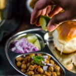 Chana masala served with a side of pav, onions and sprinkled with lime juice