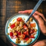 A hand holding a bowl of yogurt topped with strawberries, granola and honey