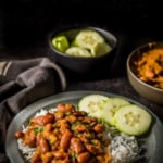 Rajma chawal served in a gray plate along with 3 cucumber slices