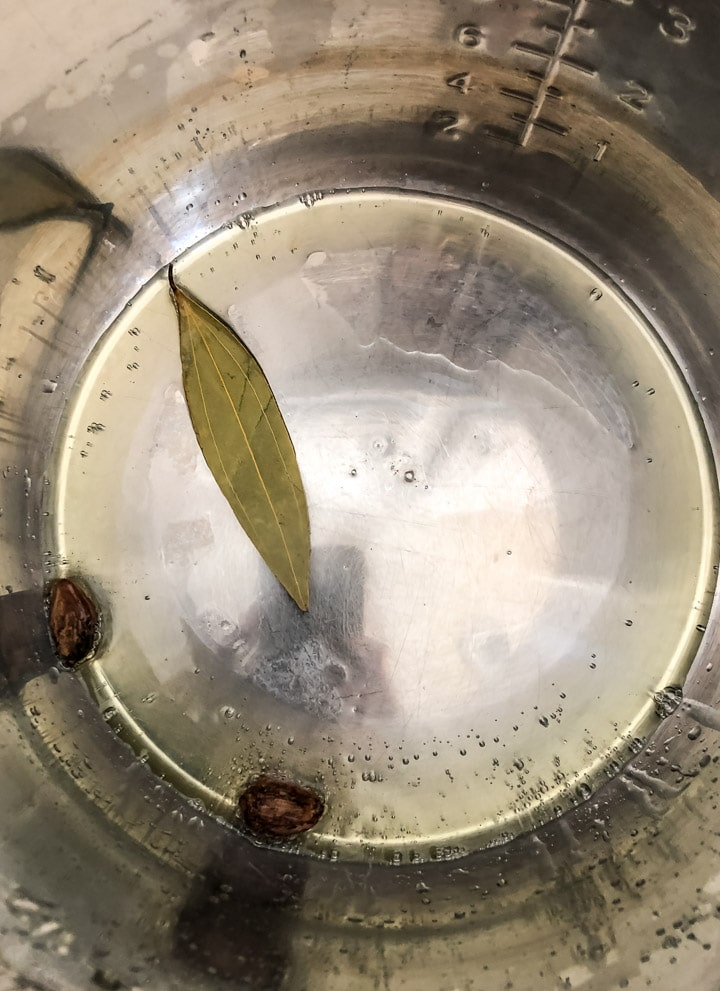 Black cardamom and bay leaf is added to oil in Instant Pot
