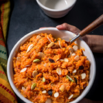 An overheat shot of carrot halwa sprinkled with nuts. It surrounded by a colorful yellow/orange and green napkin as well as empty white bowl.