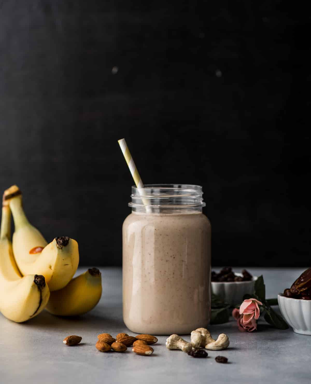 Dry fruit smoothie is served in a glass jar. Surrounding the glass jar are bananas, almonds, cashews, raisins and dates