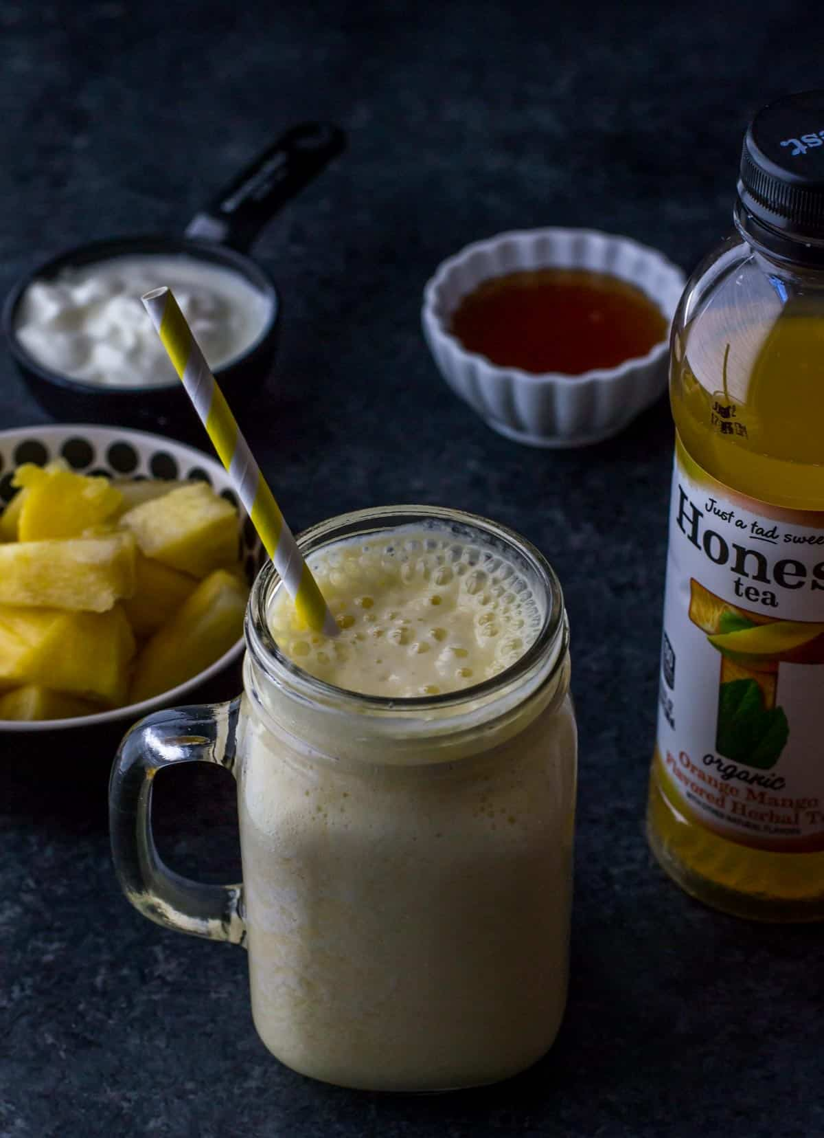 Pineapple orange mango smoothie served in a glass jar with a yellow straw. You can also see a bowl of yogurt, honey and pineapple on the side along with a bottle of Honest Tea.
