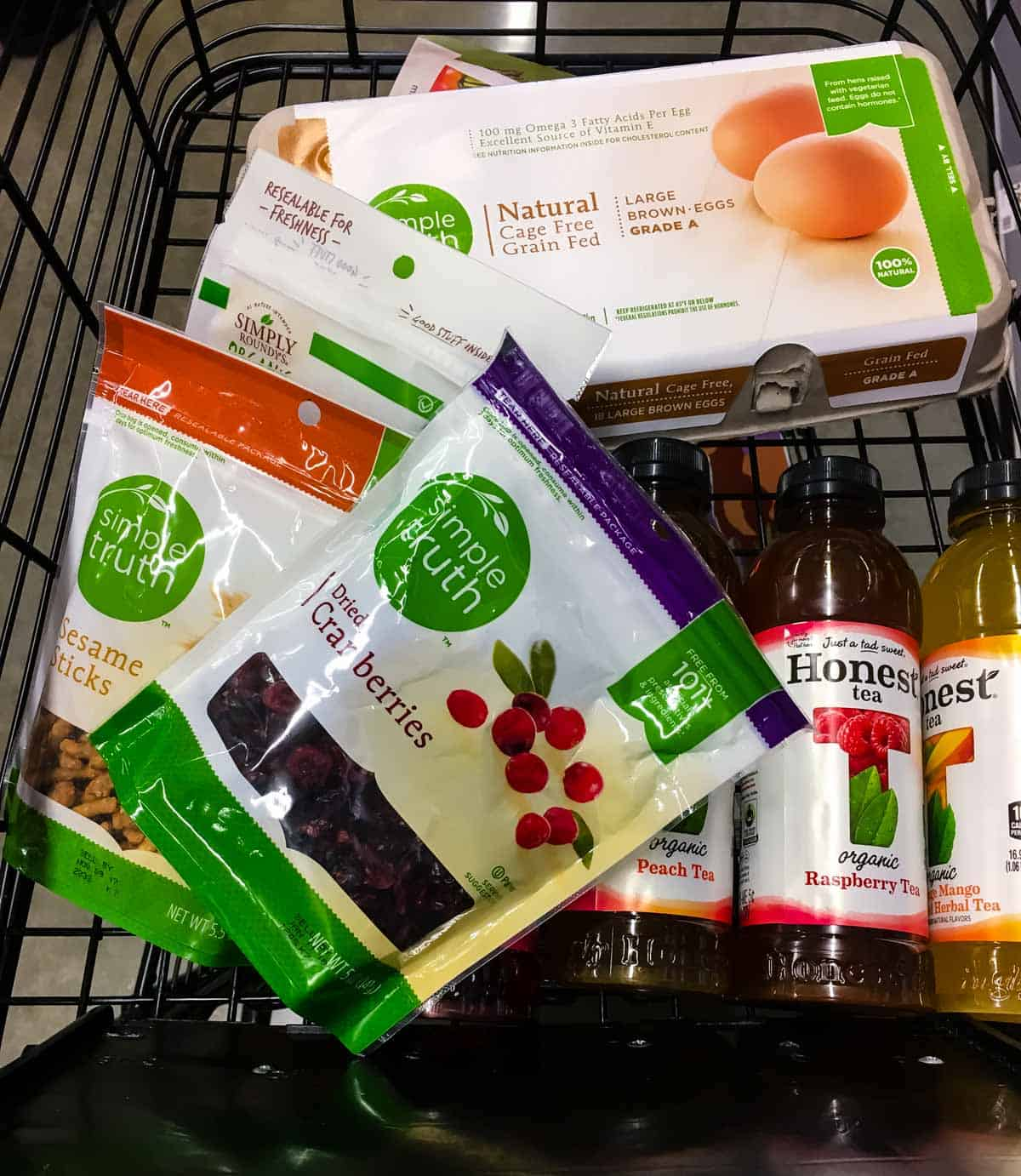 A grocery cart filled with Simple Truth snacks such as cranberries, sesame sticks. There are also a few bottles of Honest Tea and Simple Truth 24 count egg carton