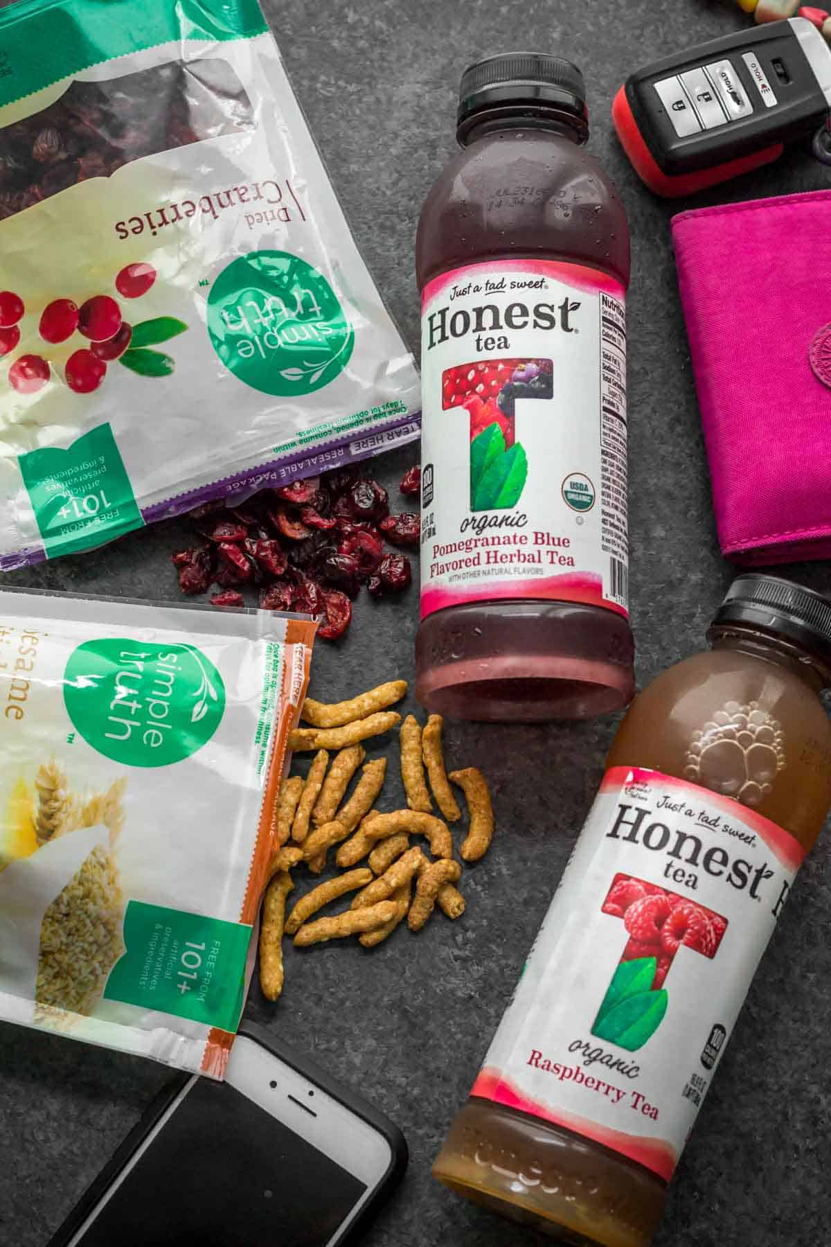 Open packets of Sesame sticks and cranberries with contents spilling out. 2 bottles of Honest tea along with car keys, a cell phone and a pink wallet