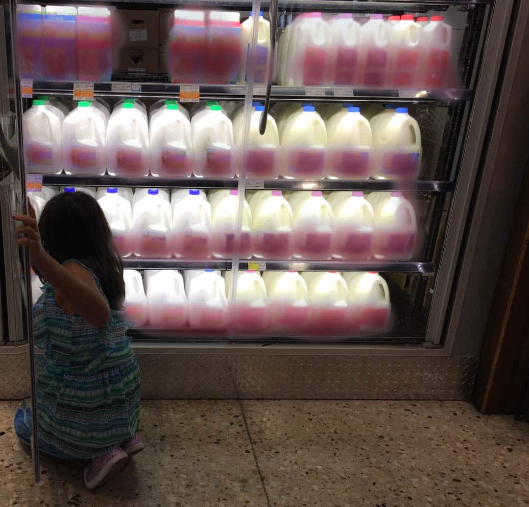 A shopping aisle in a grocery store which has cans of milk. A girl is trying to get a can of milk.