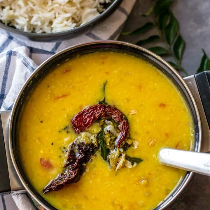 Tadka dal served in a black bowl along with rice