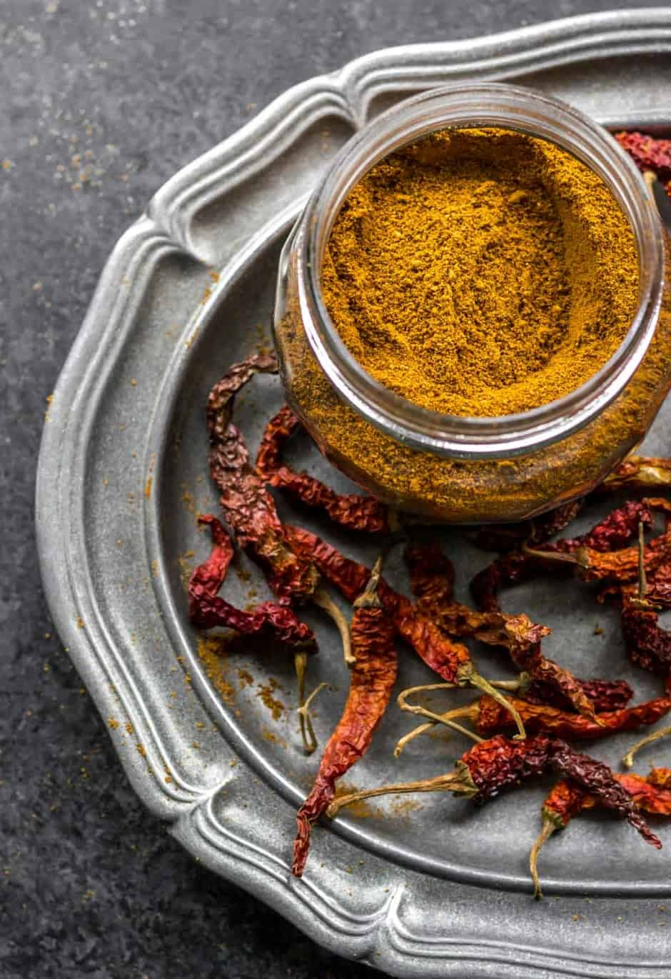 Sambar powder in a glass bottle surrounded by red chilies