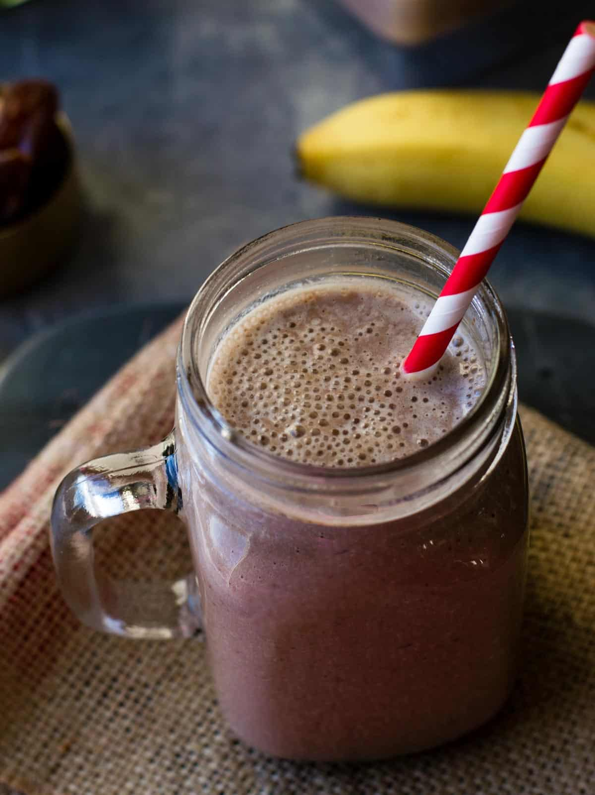 Chocolate almond smoothie served in a glass jar with a red and white straw