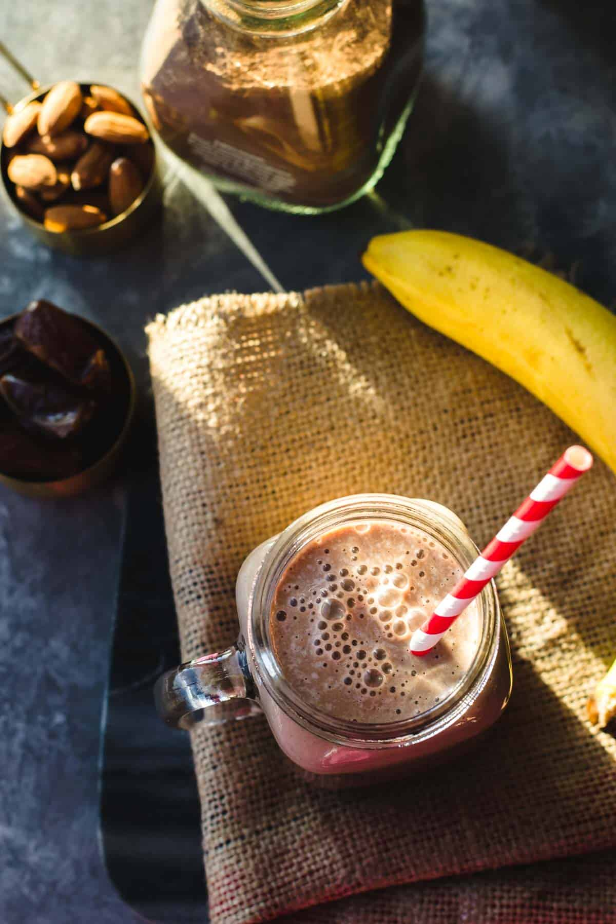 Chocolate almond smoothie served with a red and with straw. There is also a cocoa mix bottle along with almonds, dates and bananas in this picture.