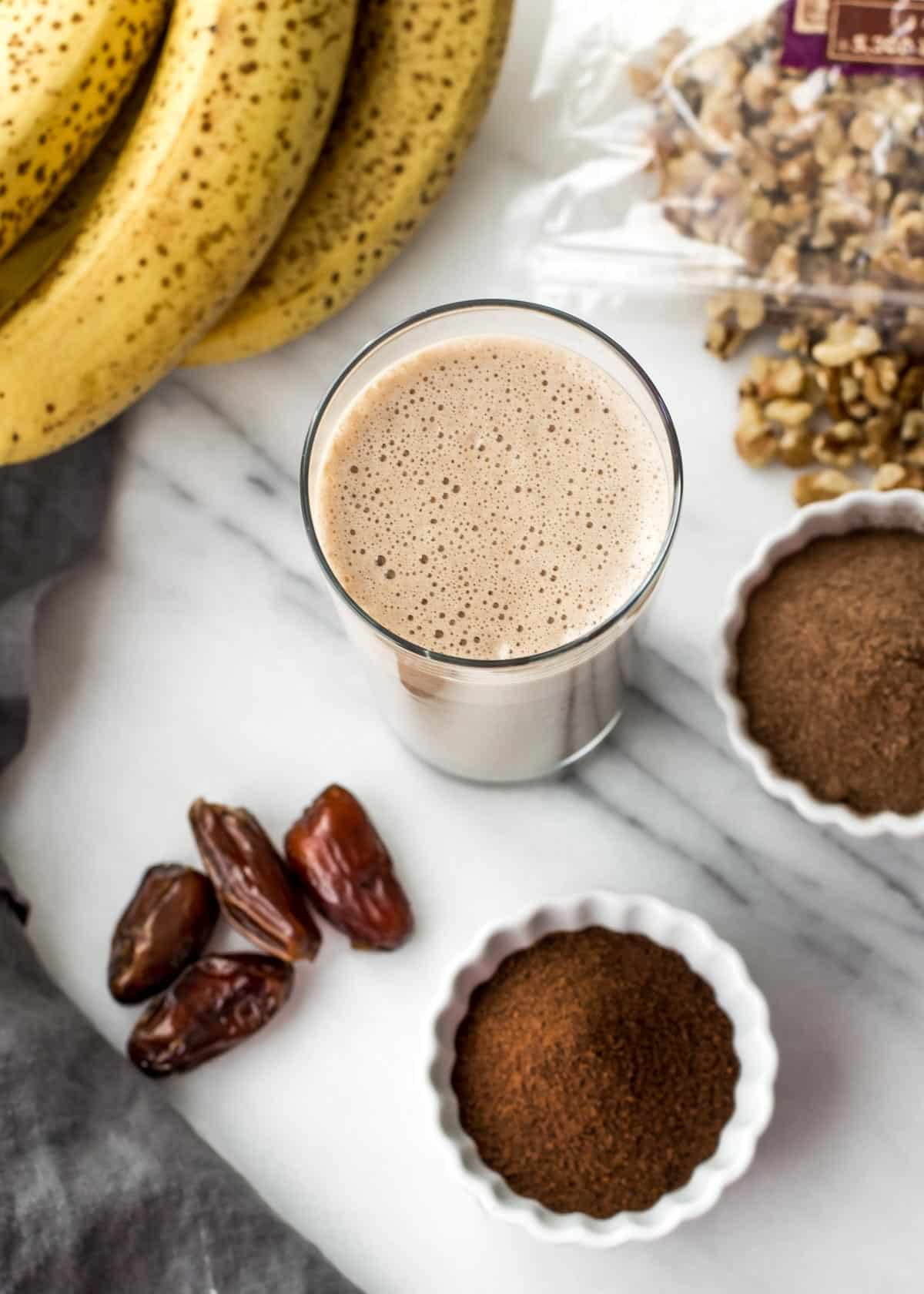 Overhead shot of Coffee walnut smoothie served in a tall glass. The picture also has bananas, walnuts, dates, coffee and cocoa mix in a white bowl.