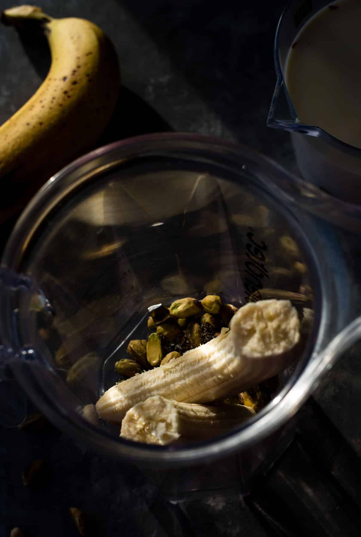 Ingredients for Kesar Pista smoothie in a blender with a banana on the side