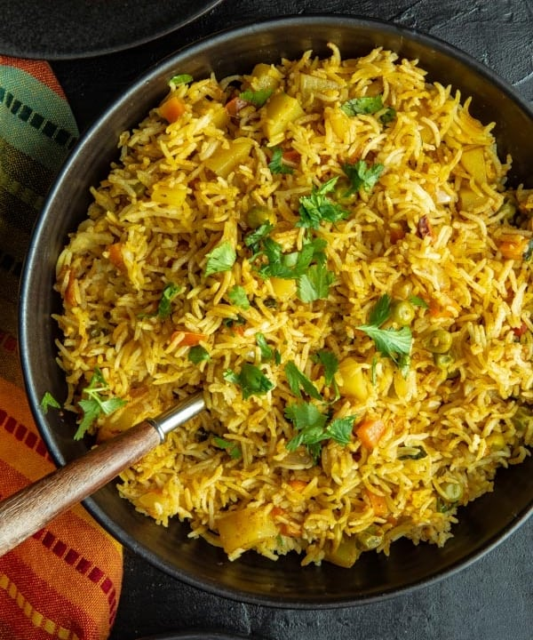 An overhead shot of Instant Pot Vegetable Biryani in a black bowl accompanied by a orange and green napkin