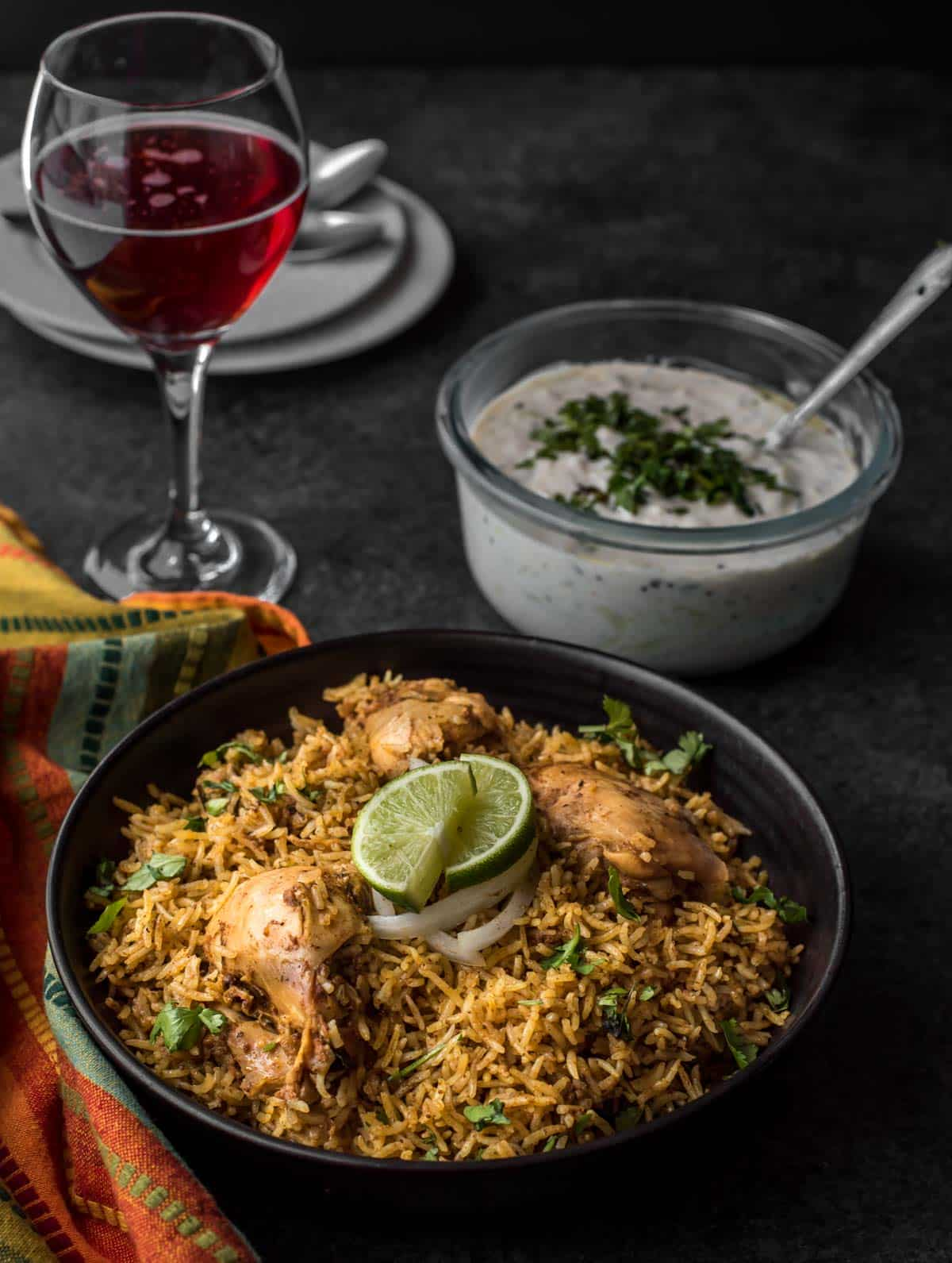 Chettinad Chicken biryani served in a black bowl with a side of raita and red sparkling wine