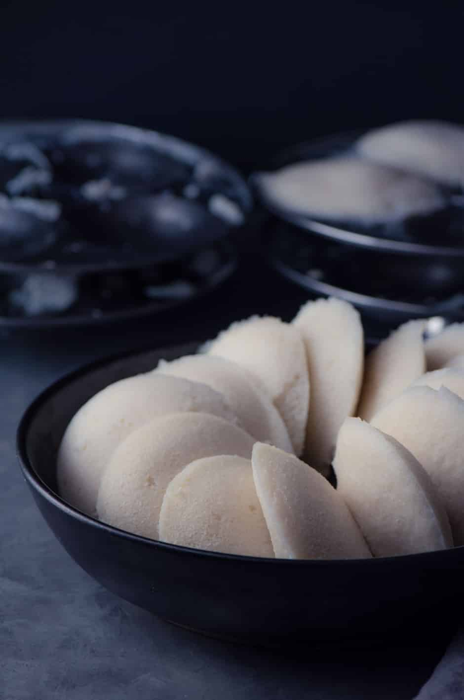 Soft Idlis made in Instant Pot served in a black bowl