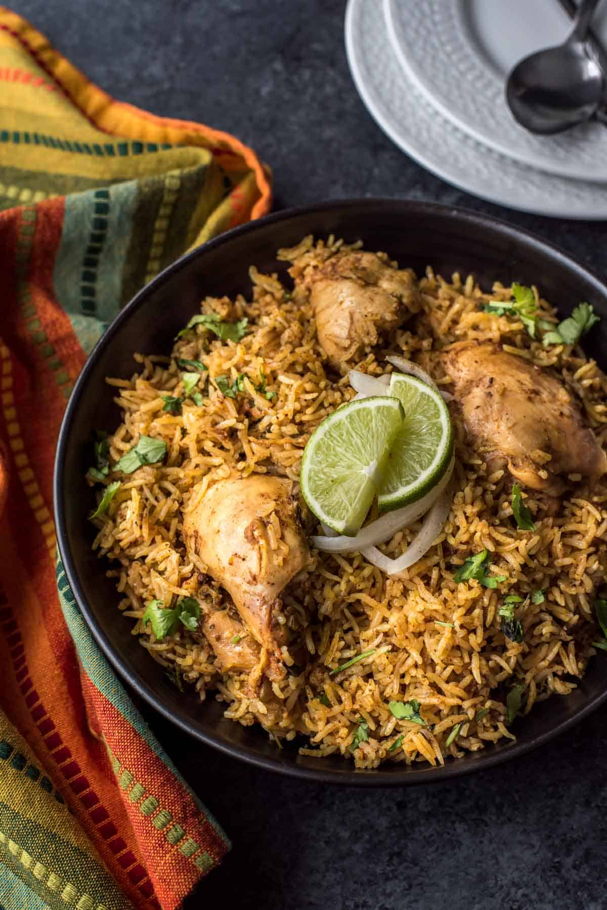 Chettinad Chicken biryani served with onions and lime in a black bowl