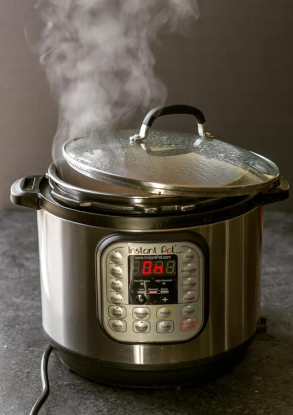 Curry sauce cooking in an Instant Pot with a glass lid partially covering it