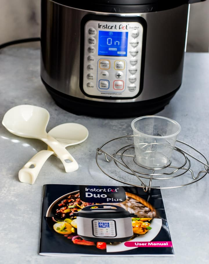 Instant Pot Duo Plus - What's inside the box - steam rack with handles, recipe booklet, serving spoon, soup spoon, and a measuring cup