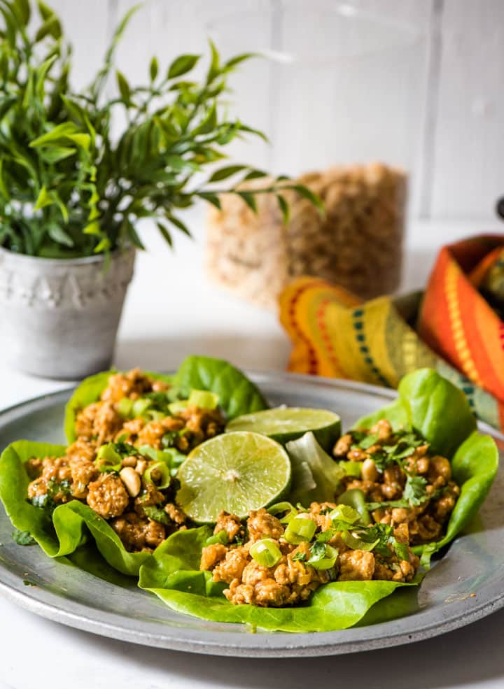 Chicken lettuce wraps served with a side of lemon