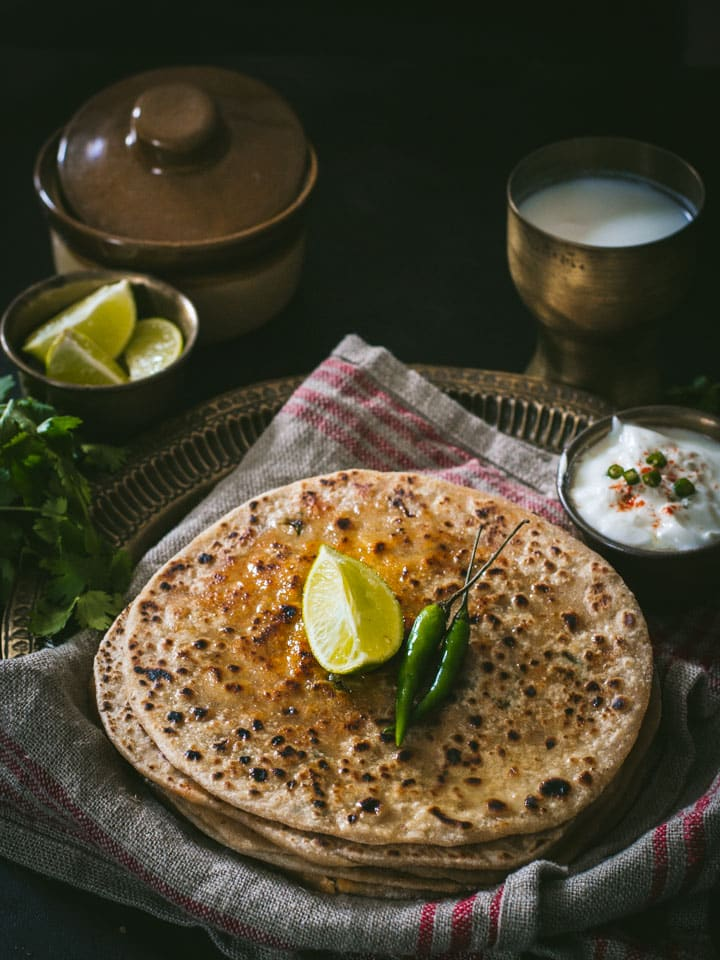 Paneer paratha served with a side of yogurt, lemon and green chilies