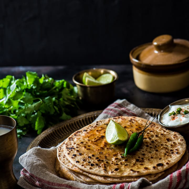 Paneer paratha served with yogurt and lime slices along with green chilies