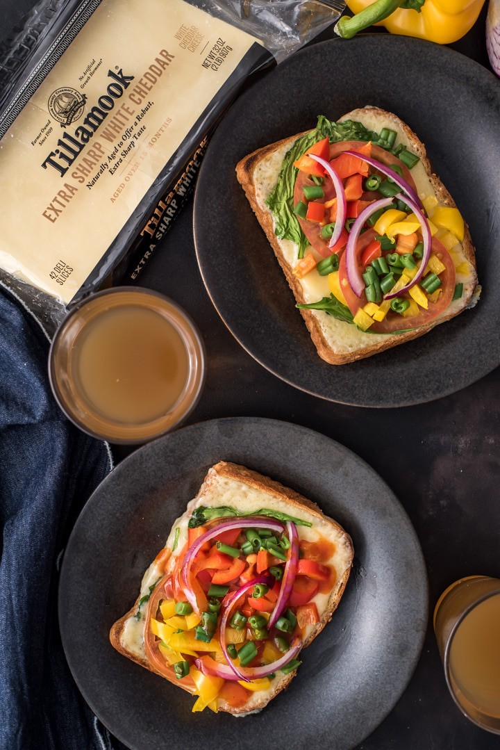 Open-faced sandwiches served in black plates. Tillamook cheese slices and two glasses of tea are kept next to them