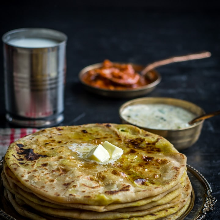Aloo paratha served with raita, pickle and lassi