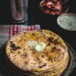Aloo paratha served with lassi, pickle, raita and dollop of butter