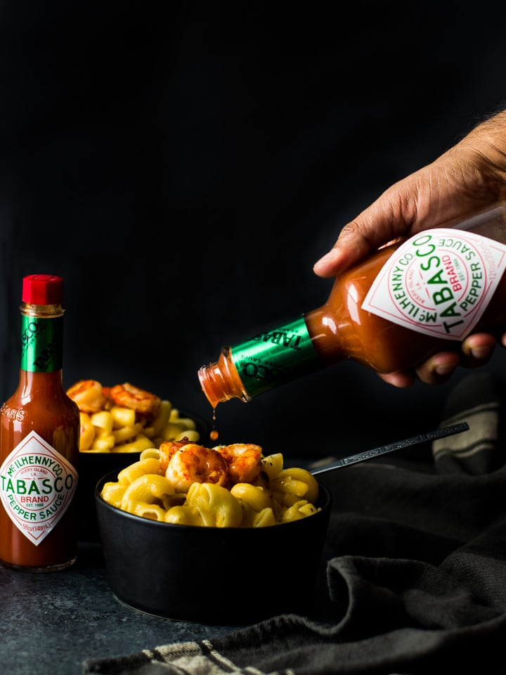 TABASCO sauce being poured over a bowl of Mac and Cheese