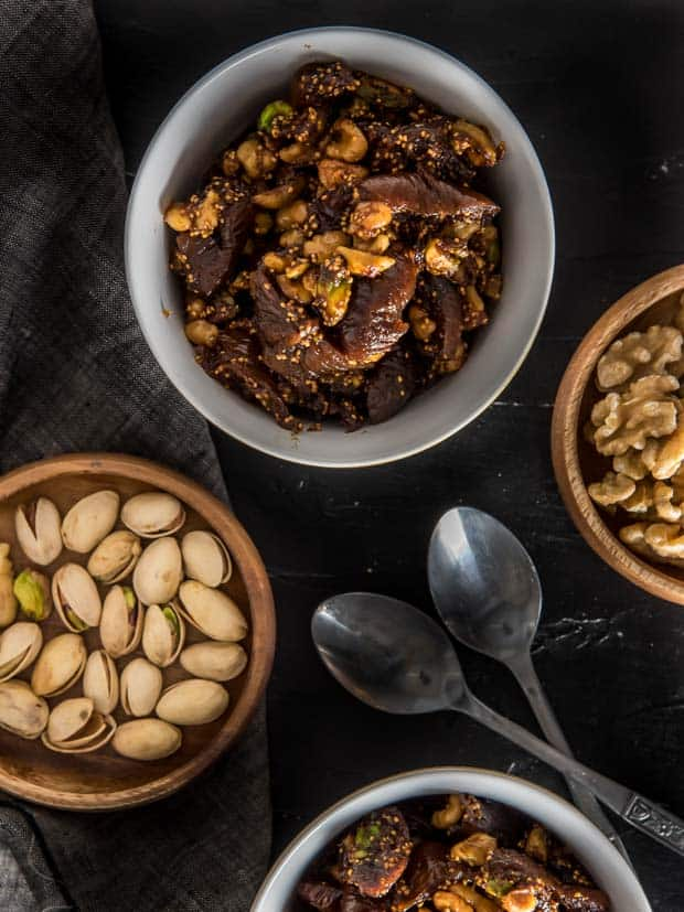 An overhead shot of fig and walnut halwa served in a white bowl with 2 spoons on the side. There are two other small wooden bowls filled with pistachios and walnuts respectively.