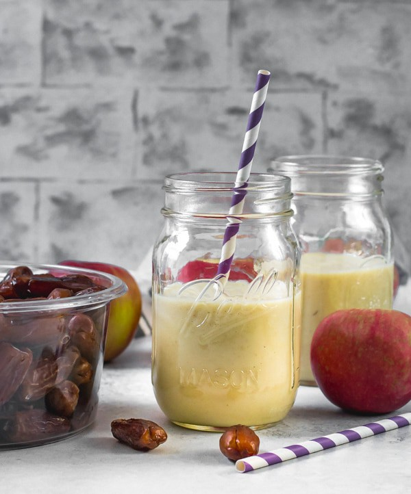 2 glass jars filled with Apple smoothie. A box of dates, an apple, along with a purple straw are on the side.