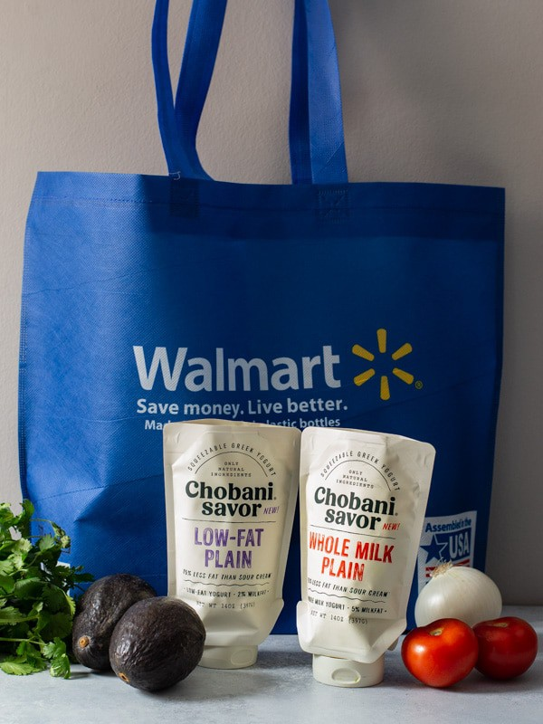 A Walmart reusable bag with cilantro on the side along with onions, tomatoes and avocados. Also. placed in front of the bag is the two flavors of Chobani Savor Topper - Whole milk and Low fat