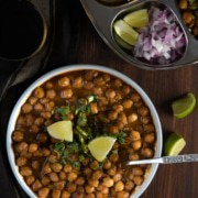 An overhead shot of chana masala sprinkled with cilantro and served with lime wedges