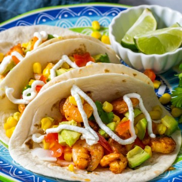 3 Shrimp tacos are lined up on a blue plate with greek yogurt dressing on top