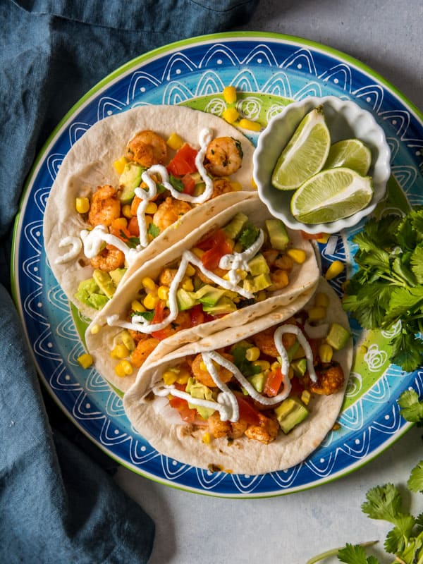 Overhead shot of 3 shrimp tacos with a white below of lime slices and a bunch of cilantro on the side.