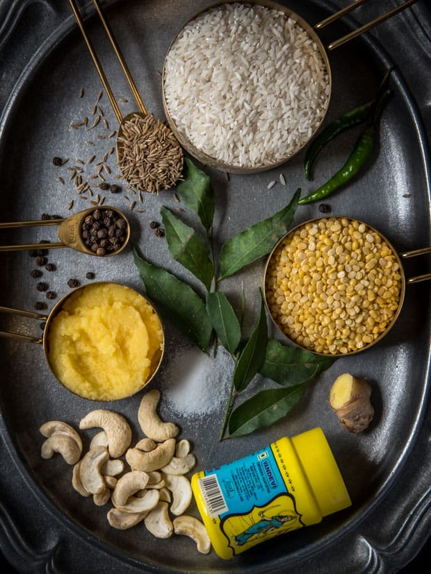 An overhead shot showing ingredients used in Ven Pongal Recipe. Includes cashews, curry leaves, salt, ginger, moong dal, rice, cumin seeds, pepper, green chilies and asafoetida.