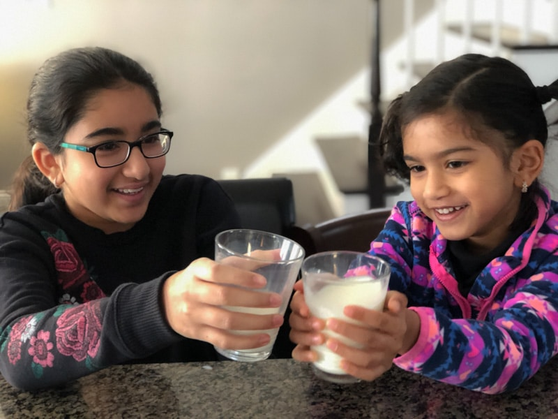 Two Asian-Indian kids are smiling and holding with each of them holding a glass of milk