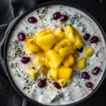 An overhead shot of pineapple raita topped with pomegranate seeds