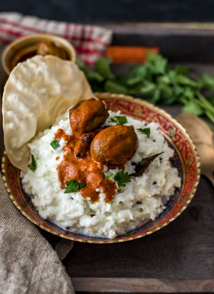 Curd rice served in a metallic gold and red bowl topped with mango pickle and papad. It is also accompanied by pickle in a ceramic brown bowl with coriander on the side