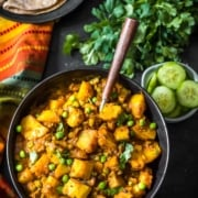 An overhead shot of Aloo matar served in a black bowl and a wooden spoon. A bunch of coriander, cut cucumber slices along with rotis accompany this dish