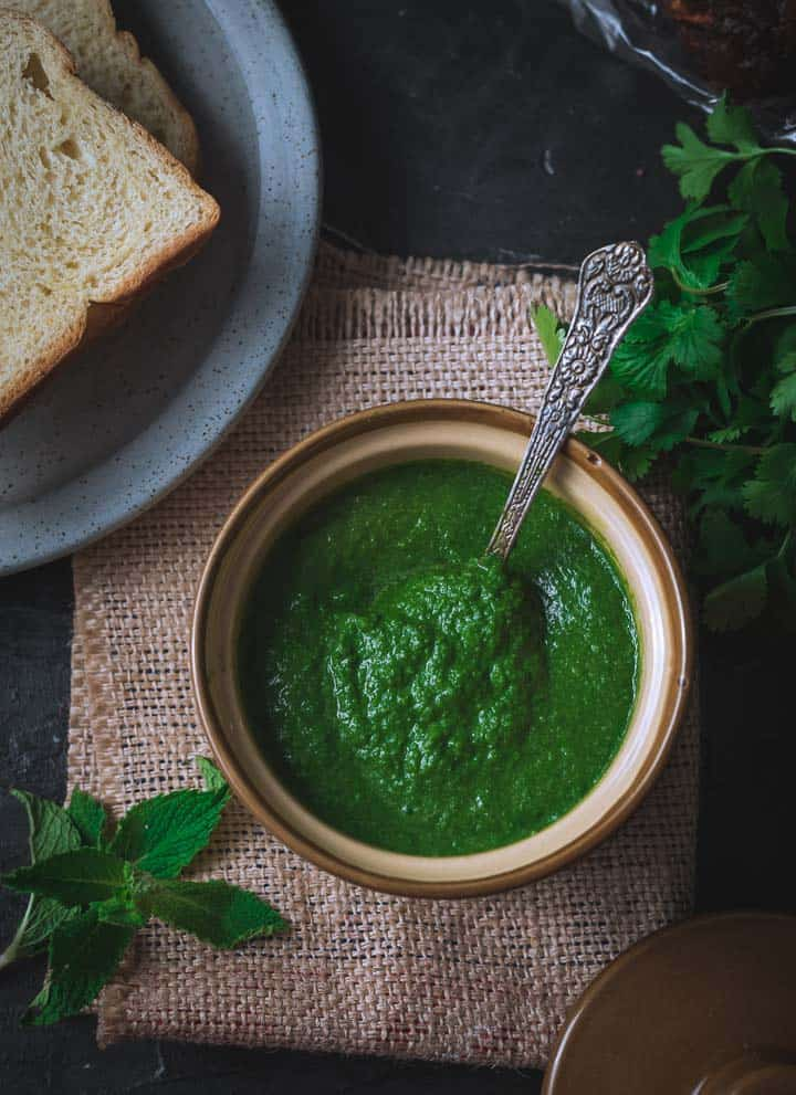 An overhead shot of coriander mint chutney placed in a porcelain bowl. There is a grey plate with bread slices, a bunch of cilantro and a few mint leaves on the side.