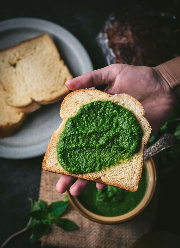 Bread slathered with green chutney is placed on a palm. There are additional bread slices kept on a grey plate.