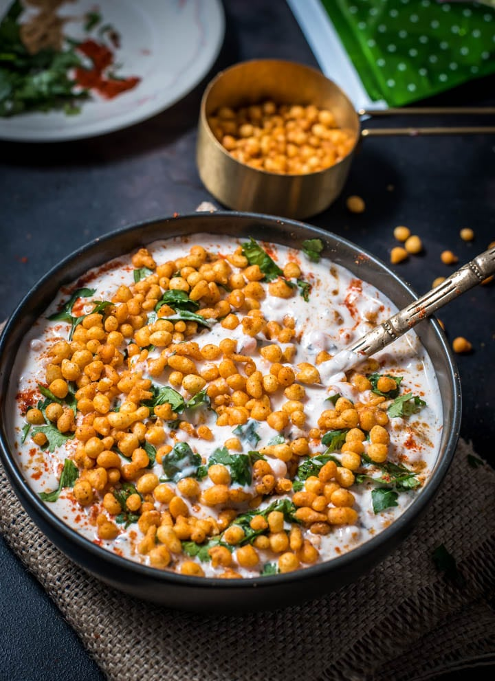Boondi raita recipe is placed on a black bowl with a golden spoon. A measuring cup holds boondi raita while a glass bowl holds remnants of boondi raita.