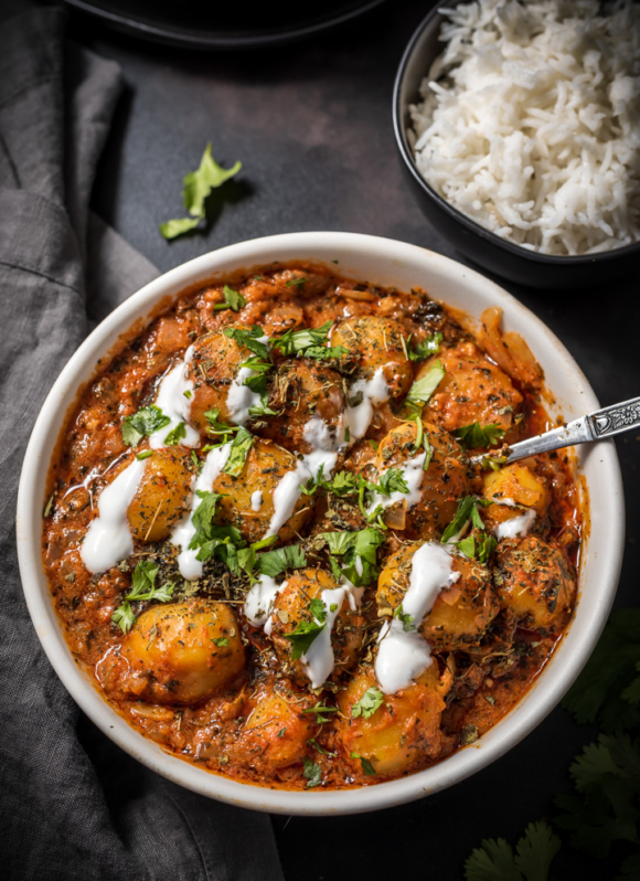 An overhead shot of Instant Pot Dum Aloo recipe served in a white bowl and garnished with fenugreek leaves, cilantro and yogurt