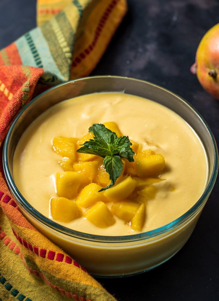 Mango raita served in a glass bowl and garnished with mint leaves