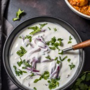 An overhead shot of onion raita served in black bowl.