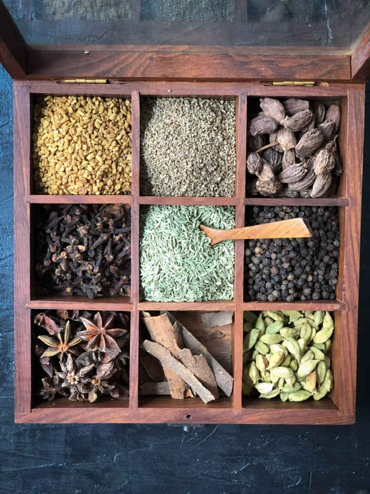 A wooden spice box with 9 compartments