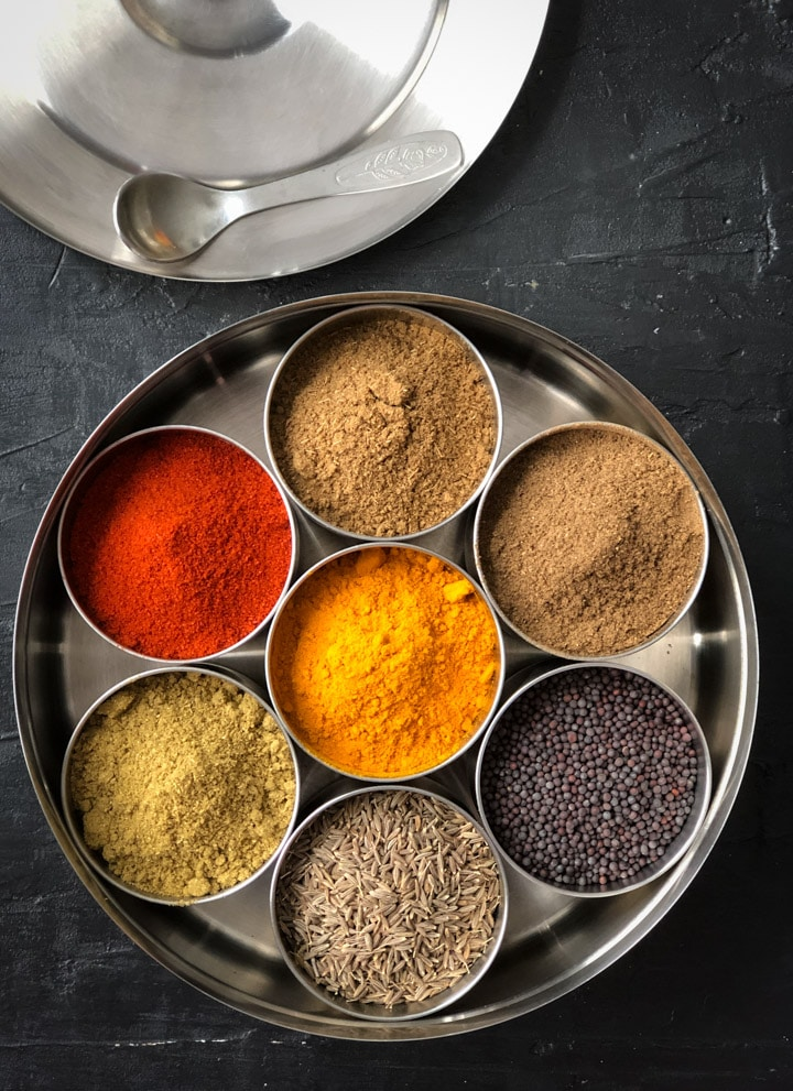 An overhead shot of an Indian spice box with 7 spices in it.