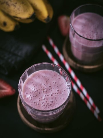 An overhead shot of strawberry banana smoothie in two glass containers and placed on a wooden bowl. There are two red and white straws on the side.